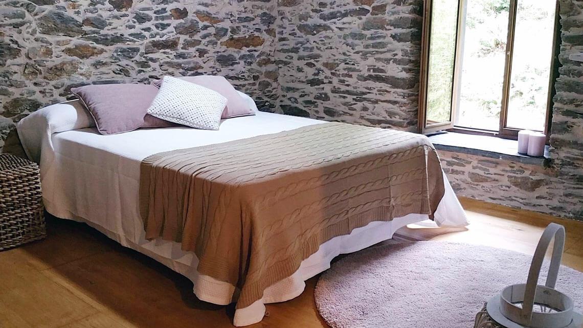 Cama de matrimonio en casa rural Muiños do Mainzoso con paredes de piedra