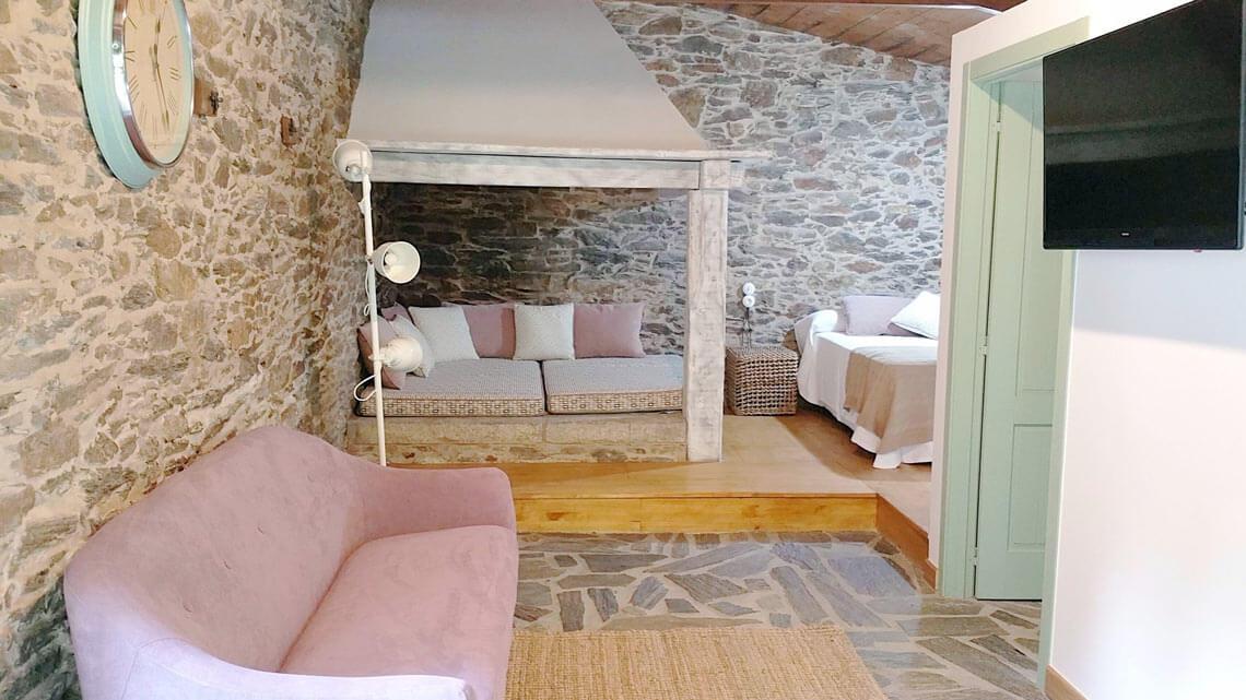 Lareira y sofá en el loft rural de Muiños do Mainzoso